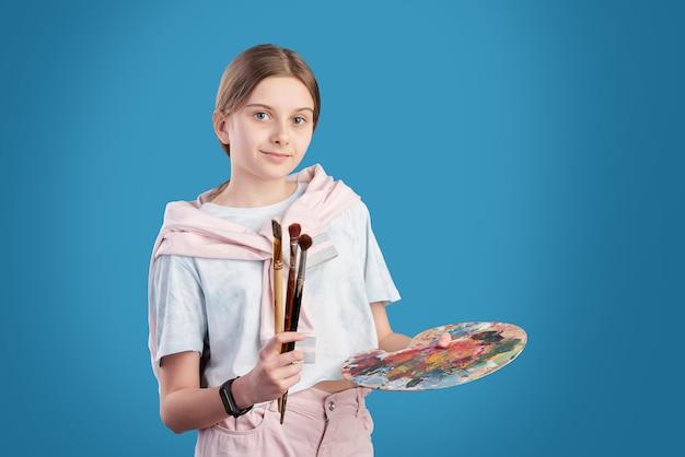 Retrato de estudiante de la escuela de arte posando con pinceles y paleta