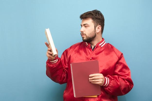 Retrato de un estudiante estadounidense con libros y cuadernos en sus manos vistiendo una chaqueta roja sobre azul