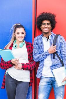 Retrato de estudiante femenino y masculino diverso sonriendo a la cámara contra la pared