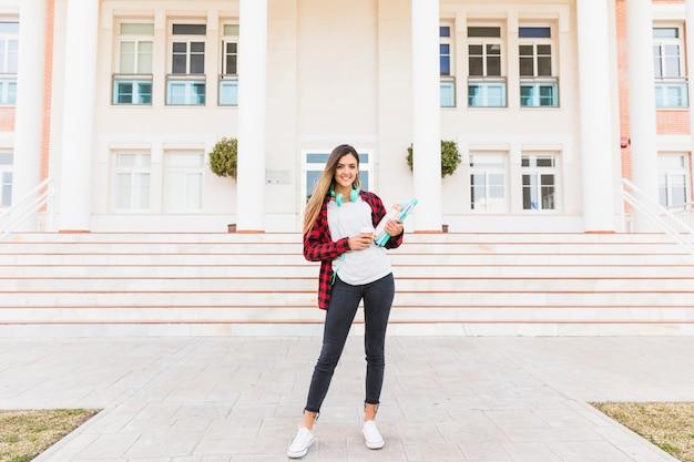 Retrato de un estudiante femenino que sostiene los libros en la mano que se coloca delante de universidad
