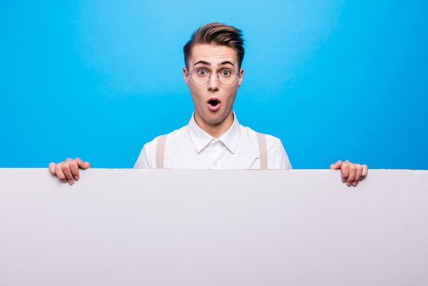 Retrato de estudiante guapo posando contra la pared azul