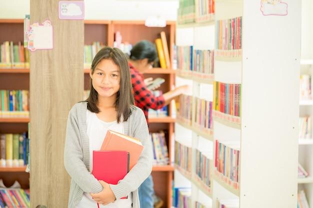 Retrato de estudiante inteligente con libro abierto que lo lee en la biblioteca de la universidad