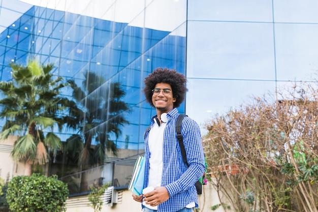 Retrato del estudiante joven masculino que se coloca delante del edificio de la universidad