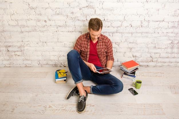 Retrato de estudiante con libros y tableta preparándose para exámenes
