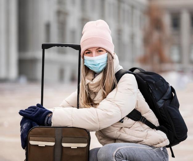 Retrato de estudiante con máscara y llevar equipaje
