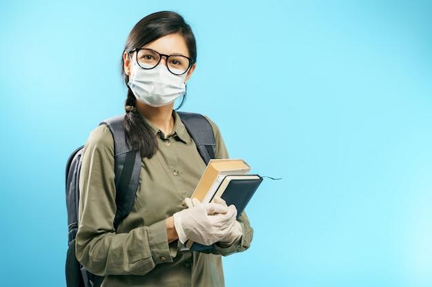Retrato de una estudiante en una máscara de protección médica y guantes sosteniendo libros sobre un fondo azul.