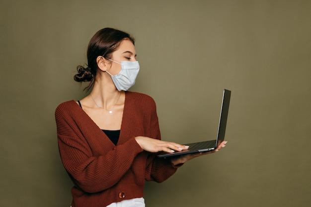 Retrato de una estudiante en una máscara protectora con una computadora portátil sobre un fondo verde. foto de alta calidad