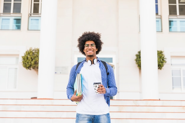 Retrato de un estudiante masculino adolescente afro feliz que sostiene los libros y la taza de café para llevar que se coloca delante de universidad