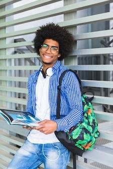 Retrato de un estudiante masculino afro sonriente sosteniendo el libro en la mano apoyado contra la pared