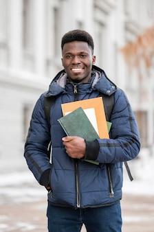 Retrato de estudiante masculino con libros