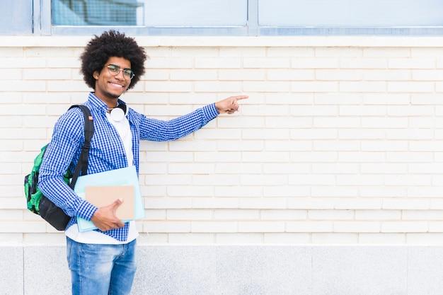 Retrato de un estudiante masculino sonriente africano que sostiene los libros en la mano que señala el dedo en la pared pintada blanca