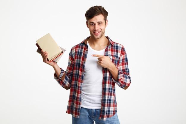 Retrato de un estudiante masculino sonriente que sostiene los libros
