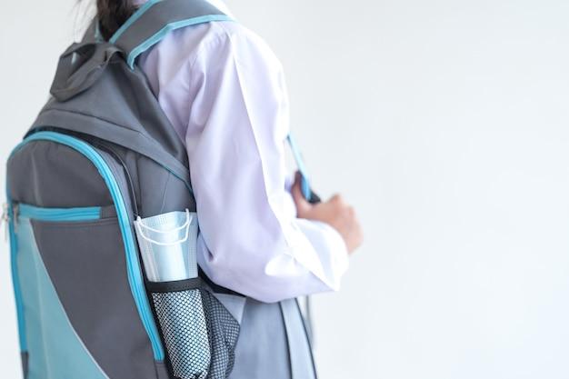 Retrato de un estudiante niño alegre lleva una mascarilla aislada sobre fondo blanco, sonríe y mira a la cámara. concepto de regreso a la escuela stock photo