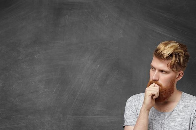 Retrato de estudiante pelirroja con mirada dudosa e indecisa tratando de resolver un problema matemático difícil o recordando algo, tocando su barba peluda mientras está de pie en la pizarra en clase