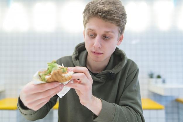 Retrato de un estudiante que parece hambriento en el sándwich en sus manos.
