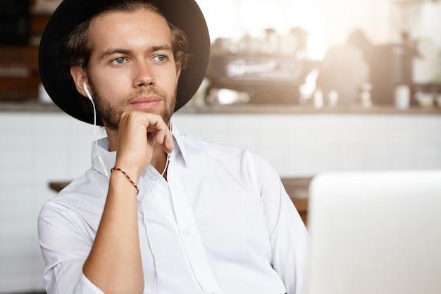 Retrato de estudiante serio con camisa blanca y sombrero negro con expresión pensativa, mirando hacia adelante mientras escucha audiolibros en auriculares, sentado en el interior frente a una computadora portátil abierta