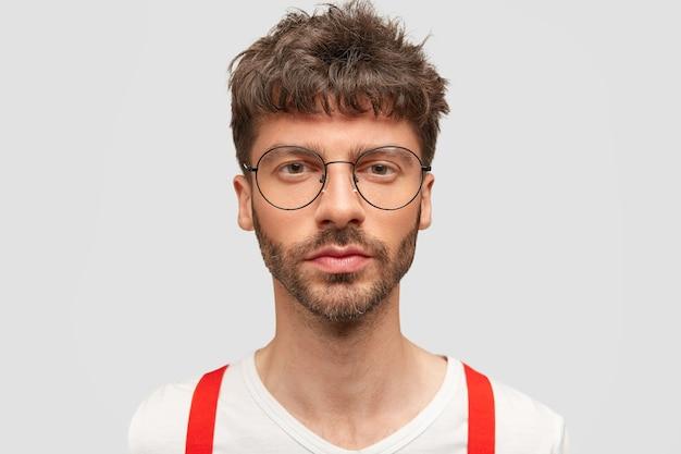 Retrato de estudiante serio hombre atractivo en gafas, vestido elegantemente, viene para aprobar el examen, confía en sí mismo en su conocimiento, posa contra la pared blanca