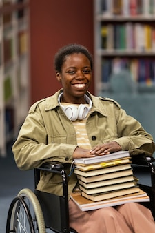 Retrato de estudiante en silla de ruedas en la biblioteca