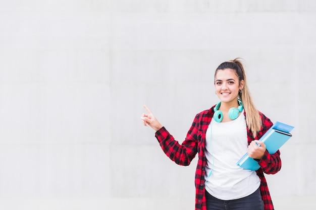 Retrato de una estudiante sosteniendo libros en la mano apuntando con su dedo de pie contra la pared gris
