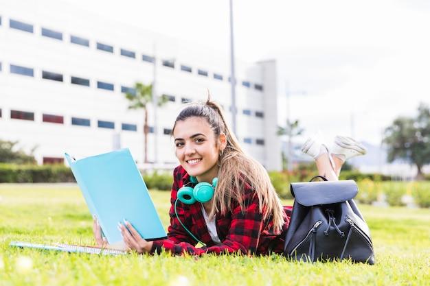 Retrato del estudiante universitario de sexo femenino sonriente que miente en la hierba verde que sostiene el libro disponible