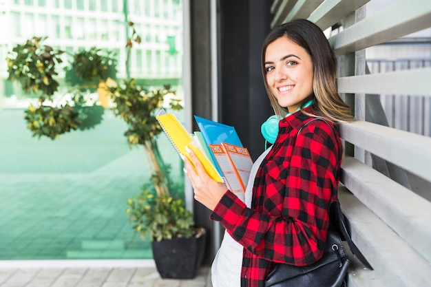 Retrato de un estudiante universitario de sexo femenino sonriente que sostiene los libros en la mano que se inclina en la pared