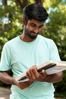 Retrato de estudiante universitario sosteniendo algunos libros