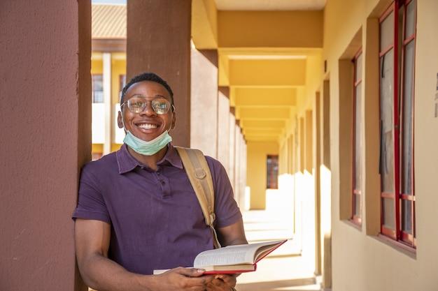 Retrato de un estudiante varón sonriente sosteniendo un libro y sonriendo