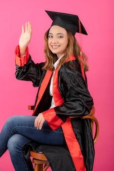 Retrato de estudiante vistiendo toga de graduación agitando su mano