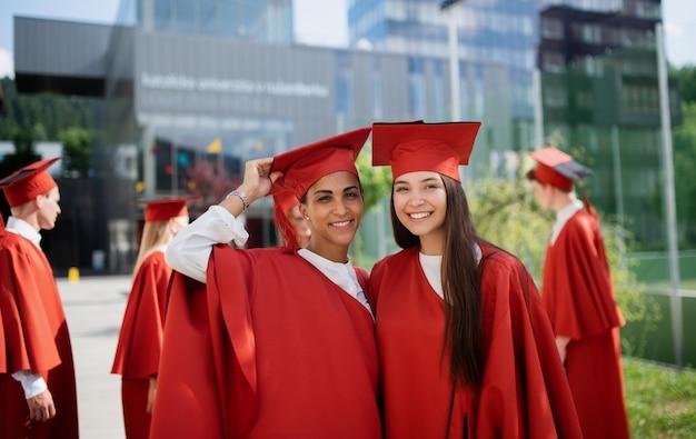 Retrato de estudiantes universitarios alegres celebrando al aire libre, concepto de graduación.