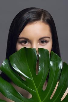 Retrato de estudio de belleza de una joven morena con maquillaje natural, piel perfecta con hojas verdes exóticas