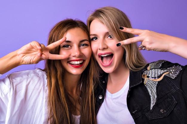 Retrato de estudio de bonitas hermanas mejores amigos mujer divirtiéndose juntos sonriendo gritando