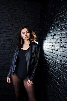 Retrato de estudio de chica morena sexy en chaqueta de cuero negro contra la pared de ladrillo.