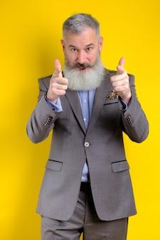 Retrato de estudio empresario maduro vestido con traje gris apunta a la cámara, te elijo concepto, fondo amarillo