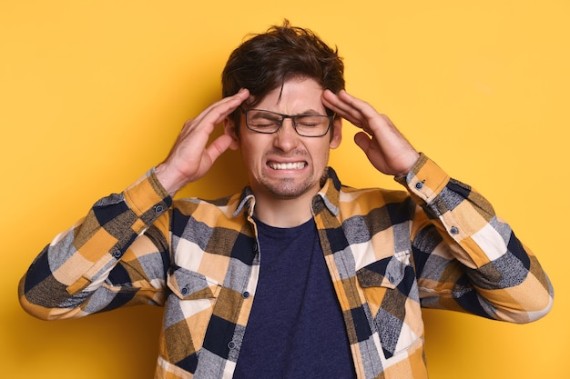 Retrato de estudio de enojado cansado de todo el hombre está furioso, tiene dolor de cabeza, experimenta estrés, exceso de trabajo.