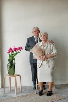 Retrato de estudio de la feliz pareja de ancianos abrazando contra la pared gris.
