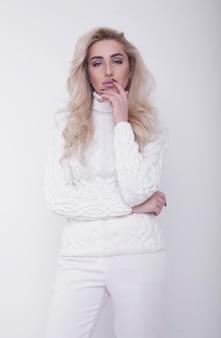 Retrato de estudio de hermosa mujer rubia de pelo largo en suéter caliente sobre fondo blanco.