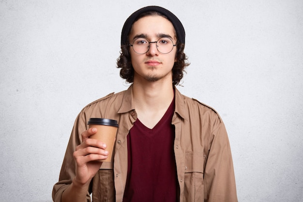 Retrato de estudio de hombre serio con taza de café aromático caliente.