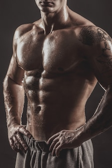 Retrato de estudio de un hombre tatuado atlético sin camisa