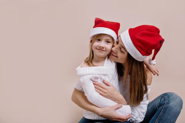Retrato de estudio interior de mujer alegre y su pequeña hija encantadora posando en una pared beige aislada