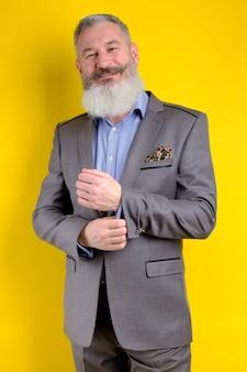 Retrato de estudio maduro guapo barbudo en traje gris mirando a la cámara, estilo de vida de profesión de trabajo, fondo amarillo.