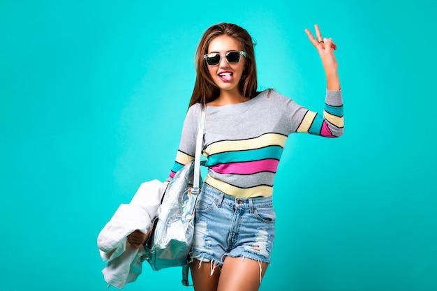 Retrato de estudio de moda de glamour chica deportiva, elegante atuendo casual, emociones lindas, gafas de sol y mochila con estilo hipster, colores pastel de primavera. mini pantalones cortos de mezclilla hipster emociones locas.