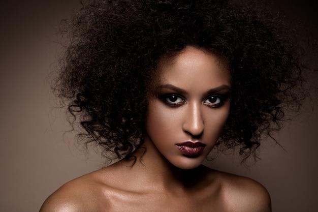 Retrato de estudio de moda de hermosa mujer afroamericana con piel mulata brillante suave perfecta, maquillaje