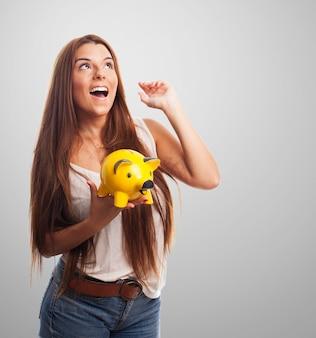 Retrato del estudio de la muchacha que sostiene hucha de color amarillo.