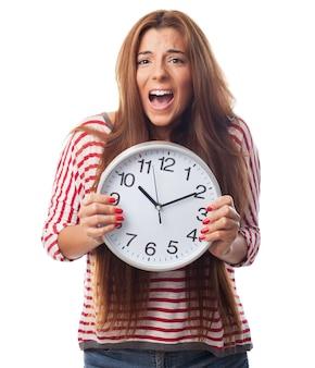 Retrato del estudio de la mujer que sostiene el reloj redondo