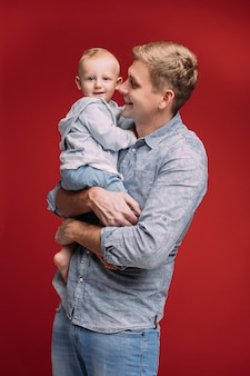 Retrato de estudio de papá feliz sonriente en camisa de mezclilla y jeans abrazando a su hijo en las manos que está mirando a la cámara. aislado sobre fondo rojo. dia del padre.