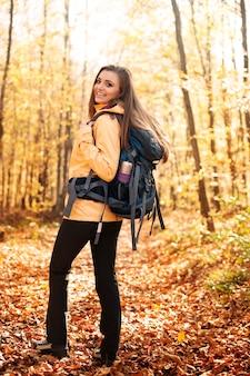 Retrato de excursionista hermosa y sonriente con mochila