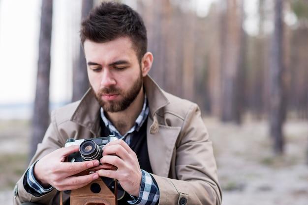 Retrato de un excursionista hombre ajustando la lente de la cámara
