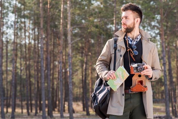 Retrato de un excursionista masculino con cámara y mapa de pie en el bosque