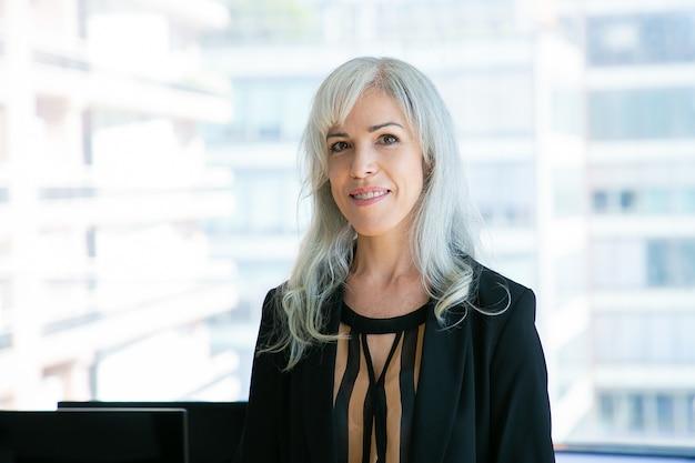 Retrato de exitosa directora ejecutiva de cabello gris y sonriente. contenido experimentado hermosa empresaria posando en la sala de la oficina. concepto de negocio, empresa, apariencia y expresión.