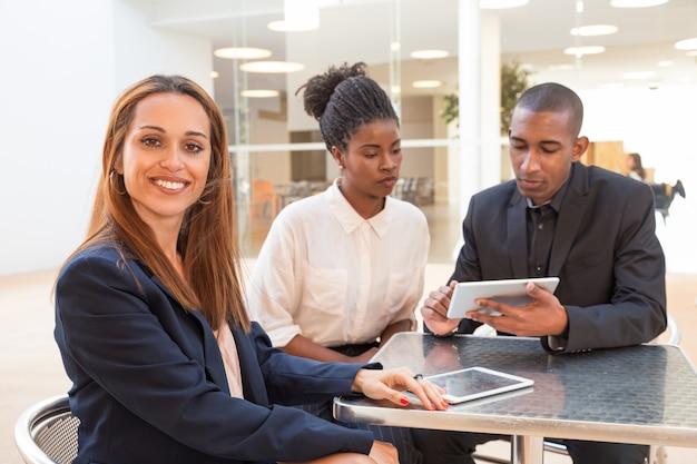 Retrato de exitosa joven empresaria con colegas
